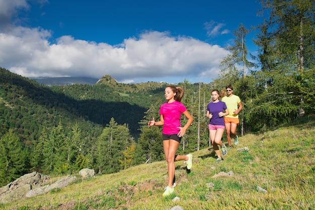 두 젊은 스포티 한 여자와 산의 경치에 잔디에서 함께 실행 소년-자연에서 조깅.