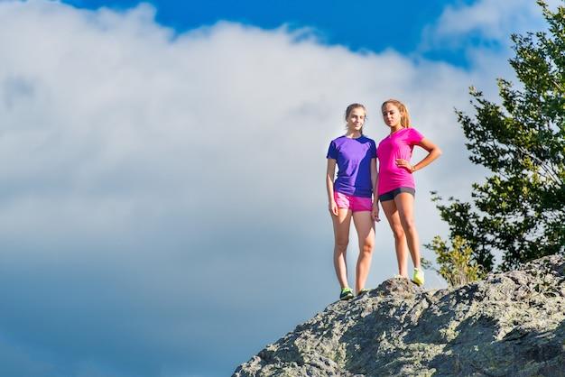 山の上に立っている2人の若いスポーティな女の子-勝利