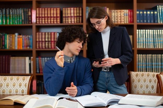 두 명의 어린 학생이 책장 근처 도서관에서 프로젝트를 논의하고 있습니다.