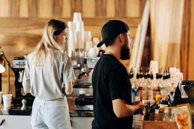 Два молодых стильных человека, худенькая блондинка и мужчина с бородой, одетые в повседневную одежду, готовят кофе в современной кофейне. .