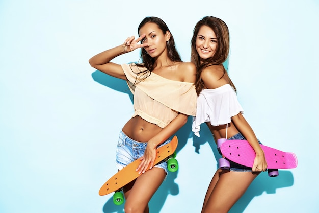 Two young stylish sexy smiling brunette women with colorful penny skateboards. hot models in summer hipster clothes posing near blue wall in studio. positive women