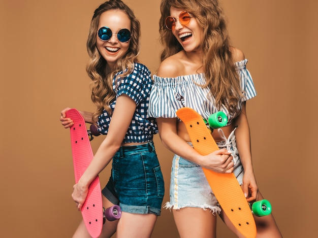 Two young stylish smiling beautiful girls with colorful penny skateboards. positive models having fun