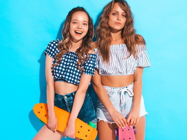 Two young stylish smiling beautiful girls with colorful penny skateboards. women in summer checkered shirt clothes posing. positive models having fun