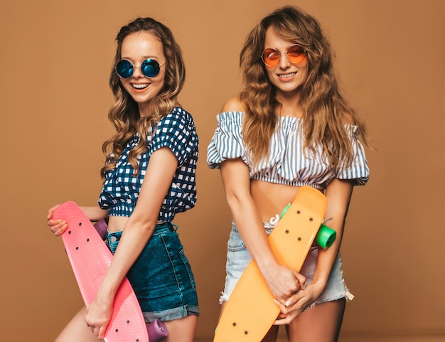 Two young stylish smiling beautiful girls with penny skateboards. women in summer checkered shirt clothes posing in sunglasses. positive models having fun