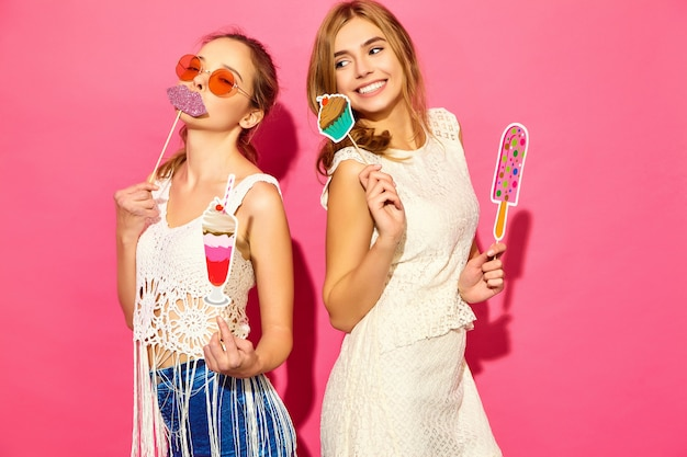 Two young stylish smiling blond women eating props sweet ice cream and fake cocktail.positive models in summer hipster clothes posing near pink wall  in sunglasses