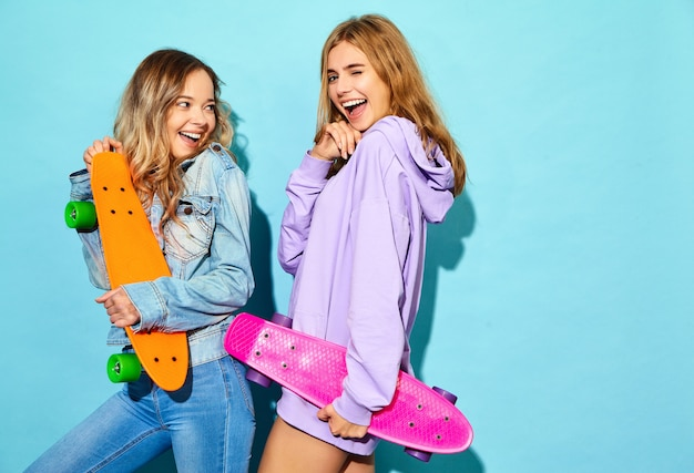 Two young stylish smiling blond women with penny skateboards. models in summer hipster sport clothes posing near blue wall . positive female