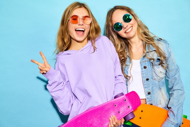Two young stylish smiling blond women with penny skateboards. models in summer hipster sport clothes posing near blue wall . positive women going crazy