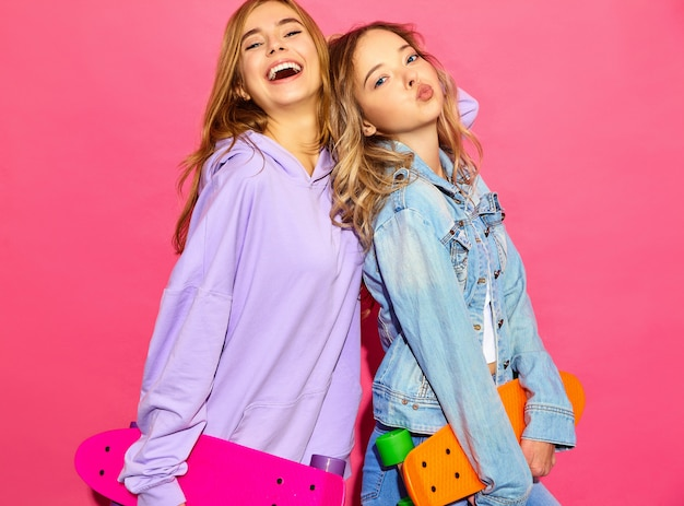 Two young stylish smiling blond women with penny skateboards. models in summer hipster sport clothes posing near pink wall . positive female