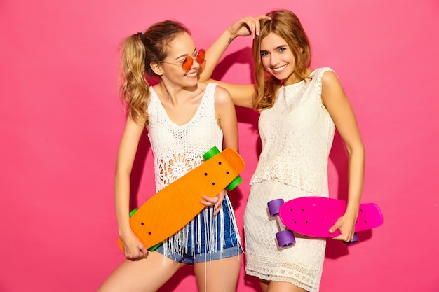 Two young stylish smiling blond women with penny skateboards. models in summer hipster white clothes posing near pink wall  in sunglasses. positive female