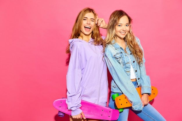 Two young stylish smiling blond women with penny skateboards. women in summer hipster sport clothes posing near pink wall . positive models winking