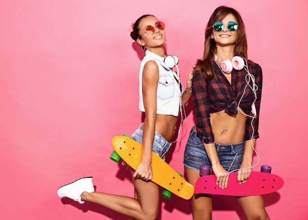 Two young stylish smiling  brunette women with penny skateboards. models in summer hipster clothes posing near pink wall in studio in sunglasses with headphones