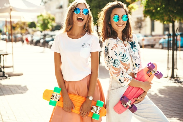 Two young stylish smiling hippie brunette and blond women models in summer sunny day in hipster clothes with penny skateboard posing