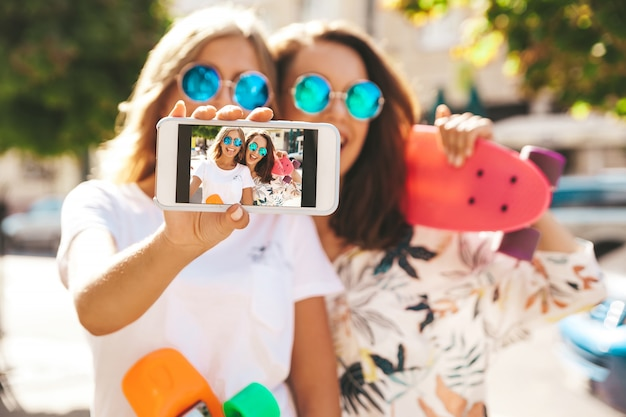 Two young stylish smiling hippie brunette in summer sunny day in hipster clothes with penny skateboard posing