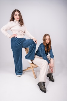 Две молодые, стильные женщины l позирует. концепция женского капсульного шкафа.