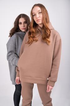 Две молодые, стильные женщины, глядя на камеру, позирует, изолированные на белом. концепция женского капсульного шкафа.