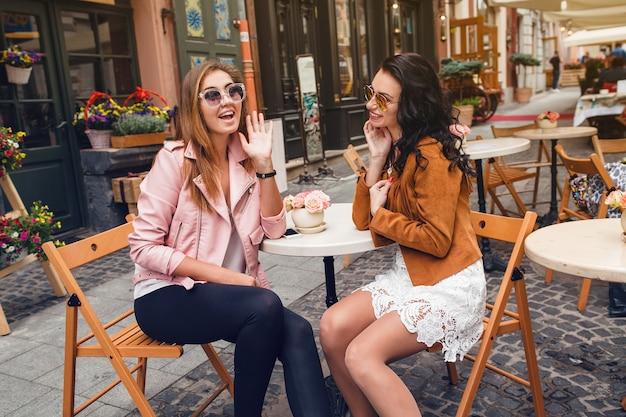 Две молодые стильные женщины, сидя в кафе