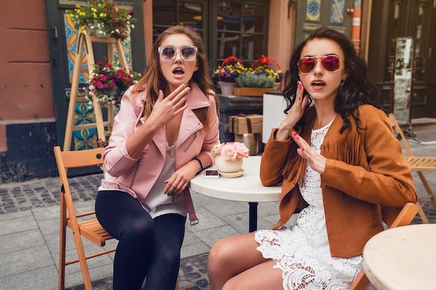 カフェに座っている2人の若いスタイリッシュな女性