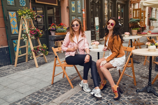 Two young stylish women sitting at cafe