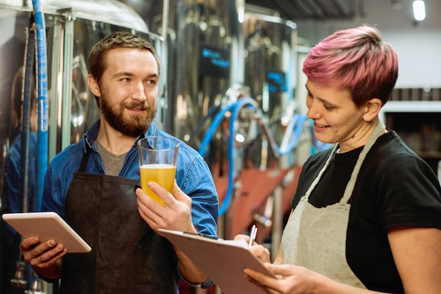Два молодых успешных пивовара обсуждают характеристики и вкус свежеприготовленного пива или лагера, в то время как женщина записывает их в мастерской