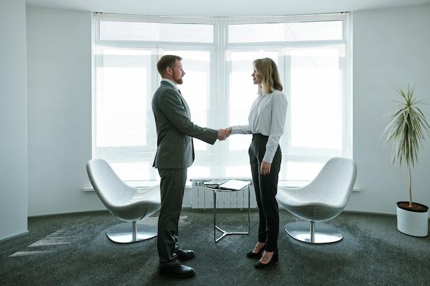 Два молодых успешных бизнес-партнера в формальной одежде, стоя у небольшого столика, кресел и большого окна в офисе во время рукопожатия