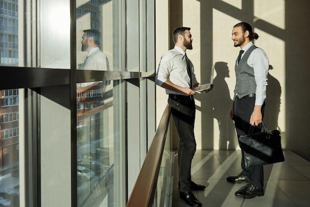 복도에서 회의에서 작업 세부 사항을 논의하는 동안 큰 창에 서있는 두 젊은 성공적인 사업가