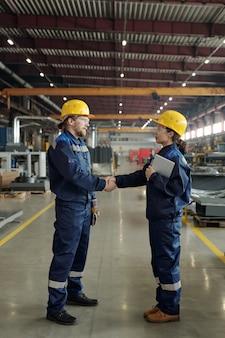 보호용 안전모와 작업복을 입은 두 명의 성공적인 젊은 엔지니어가 큰 작업장 내에서 악수하는 동안 서로를 바라보고 있습니다.