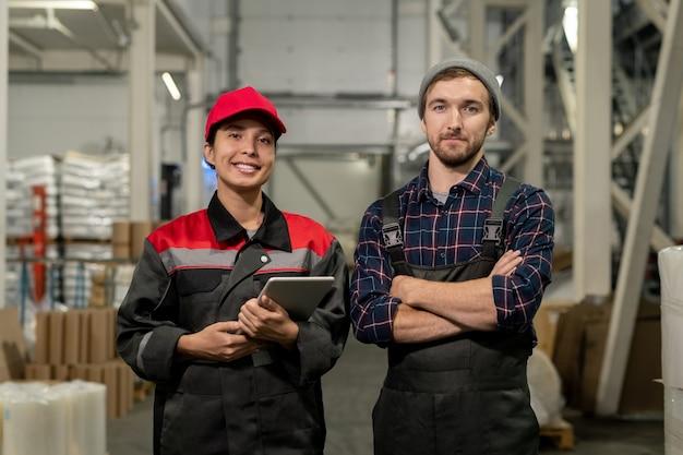 Два молодых успешных инженера большого современного завода стоят в проходе между стопками упакованного сырья на складе