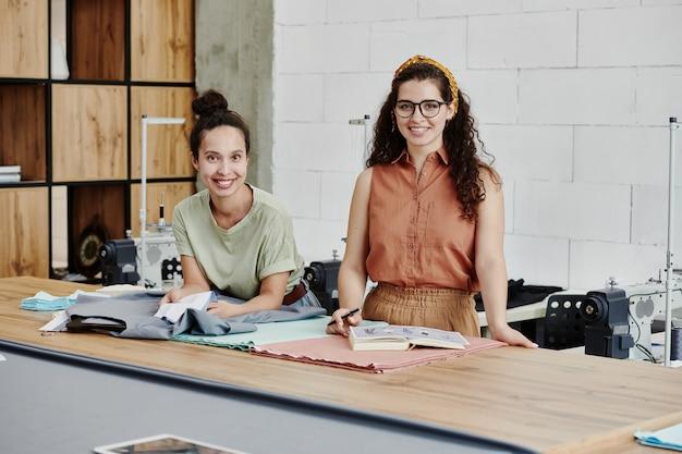 새로운 유행 패션 컬렉션 아이템을 위해 섬유를 선택하면서 미소로 당신을 바라 보는 두 젊은 성공적인 패션 디자이너