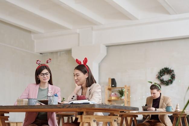 Две молодые успешные женщины-коллеги в элегантной повседневной одежде работают над отчетом для предстоящей конференции в день рождества в офисе
