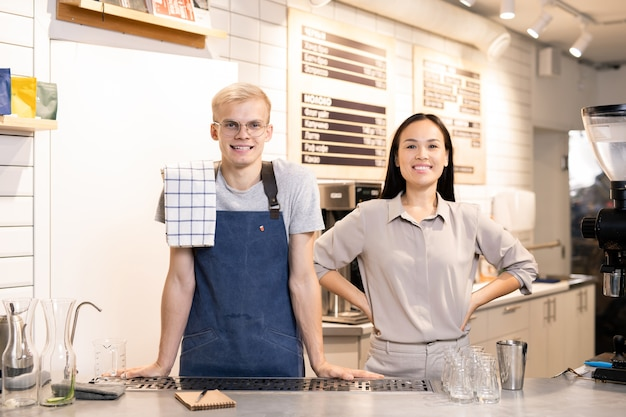 Two young successful workers of contemporary cafe or restaurant in uniform waiting for their guests by workplace