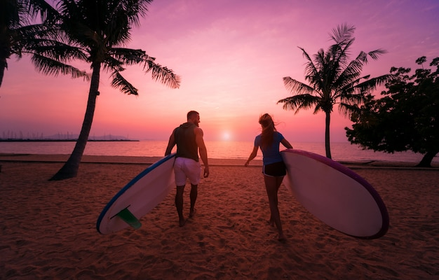 Two young surfers going into the sea with surf boards