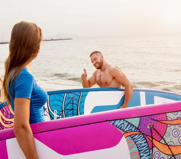 Два молодых серфера уходят в море с досками для серфинга
