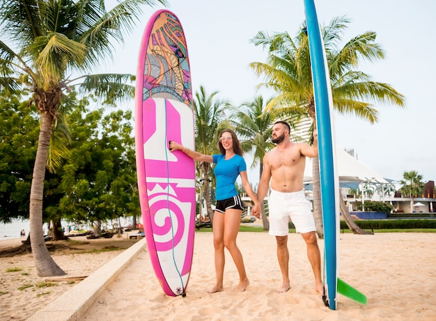 Two young surfers with boards on the beach