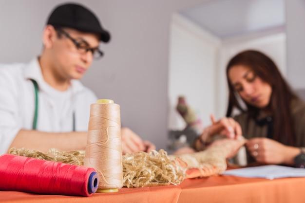 小さな縫製工場で一緒に働く2人の若い仕立て屋。