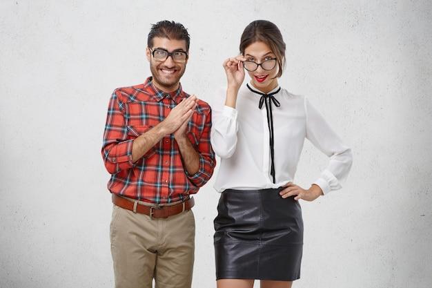 안경을 쓴 두 명의 젊은 선생님이 흥미 진진한 표정을 지녔고, 당신을 가르치거나, 수업을 할 것입니다.