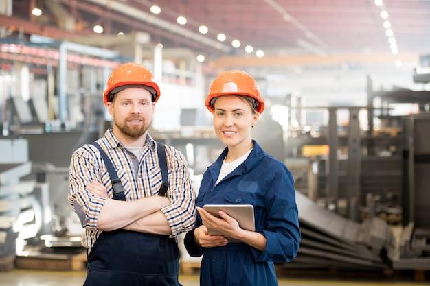 工場でグループで働く作業服と保護用のヘルメットの2人の若い技術者