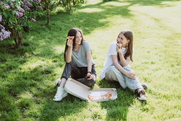 Двое молодых друзей-подростков веселятся в парке на траве и едят пиццу. женщины едят фаст-фуд. не здоровая диета. мягкий выборочный фокус.