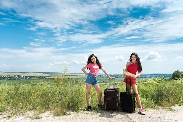 도로에서 히치 하이킹을하고 아름다운 화창한 여름날을 즐기는 휴식을 취하는 두 젊은 관광 여성