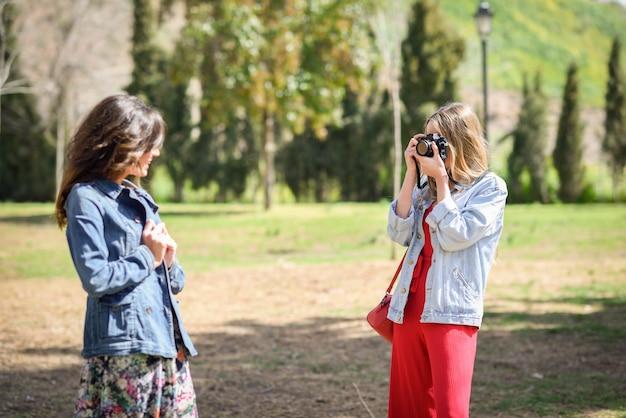 Две молодые туристские женщины фотографируют с аналоговой рефлекторной камерой в городском парке.