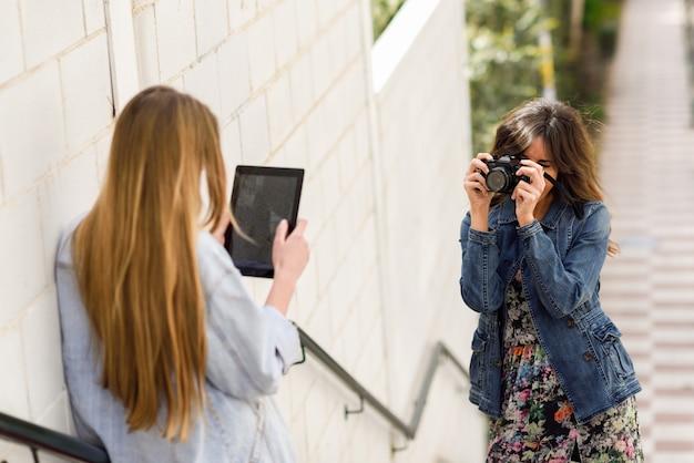 Две молодые туристы, фотографирующиеся с помощью цифровой планшеты и аналоговой рефлекторной камеры