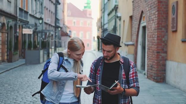Двое молодых туристов проверяют карту во время прогулки по главной туристической улице. рано утром они собираются на экскурсию.
