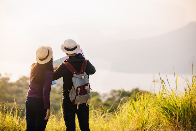 Two young tourists hiking in a nature climbing hill or mountain - man and woman trekking