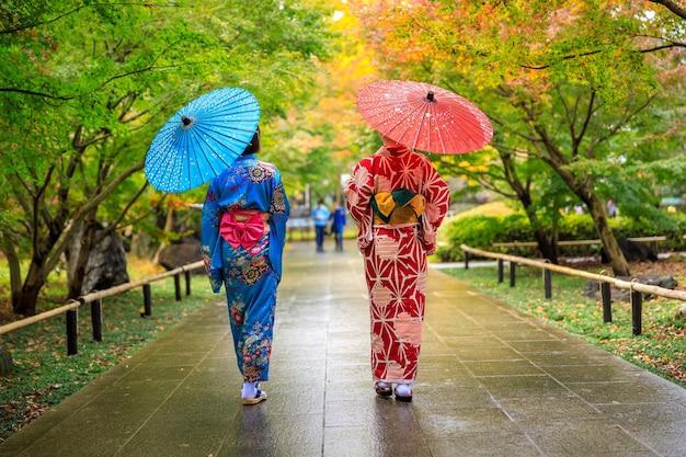Двое молодых туристов в красно-синем кимоно и зонтиком гуляли по парку в осенний сезон в японии