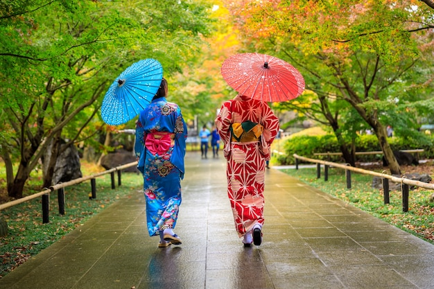 着物赤青と傘をさした2人の若い観光客が秋の日本の公園を散歩しました