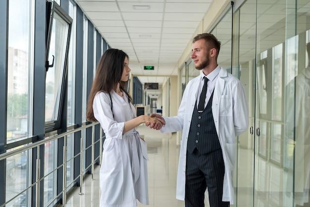 두 젊은 연수생 의사가 현대 병원 복도에서 포즈를 취합니다. 건강 개념