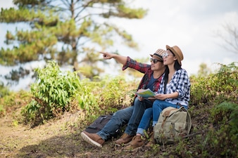 Two Young Traveler with backpack, are holding map relaxing in greens jungle and enjoying