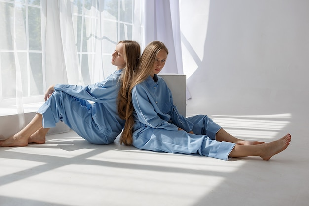 Two young twin girls in identical blue suits sitting on white cyclorama floor in studio