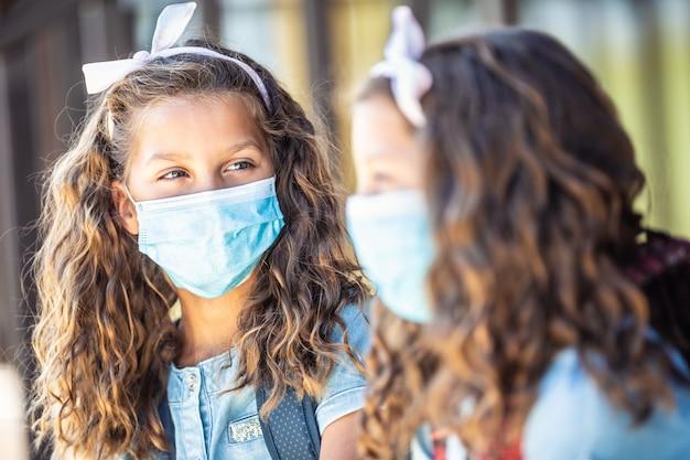 코비드-19 격리 기간 동안 마스크를 쓴 두 명의 어린 쌍둥이 자매 급우가 학교에 가는 길에 대화를 나누고 있습니다.