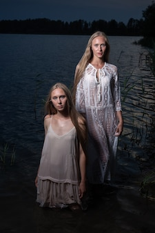 Two young twin sisters posing in light dresses in water of lake at summer night