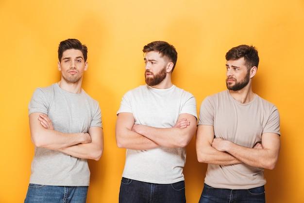 Двое молодых расстроенных мужчин смотрят на своего друга-мужчину